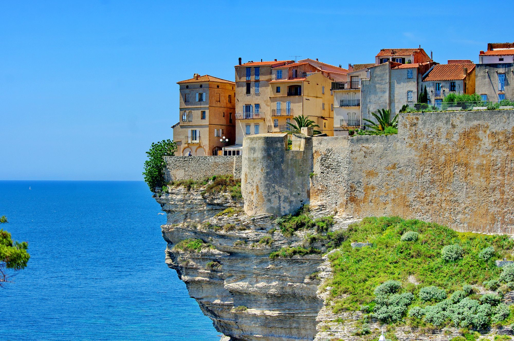 Houses perched over a cliff in Corsica - one of the best holiday destinations in the Mediterranean
