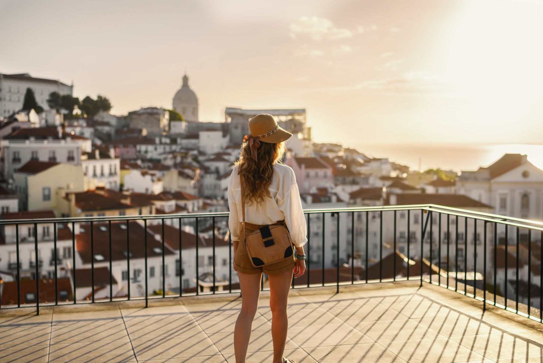 Young woman standing with her back to the camera, looking at the view of Lisbon, Portugal