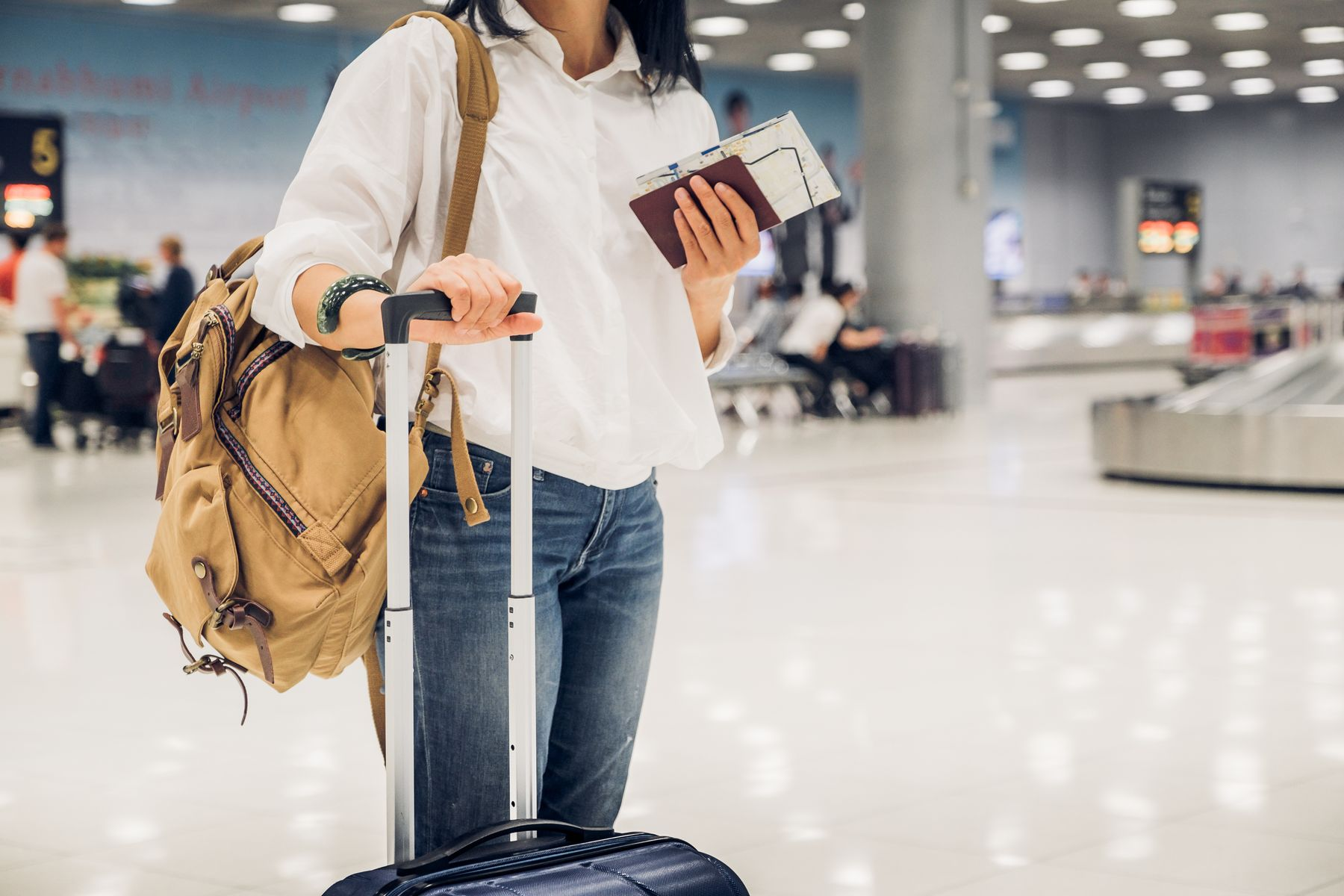 Woman standing with her suitcase handle in one hand, a canvas backpack slung over her shoulder, and her passport and ticket in the other hand