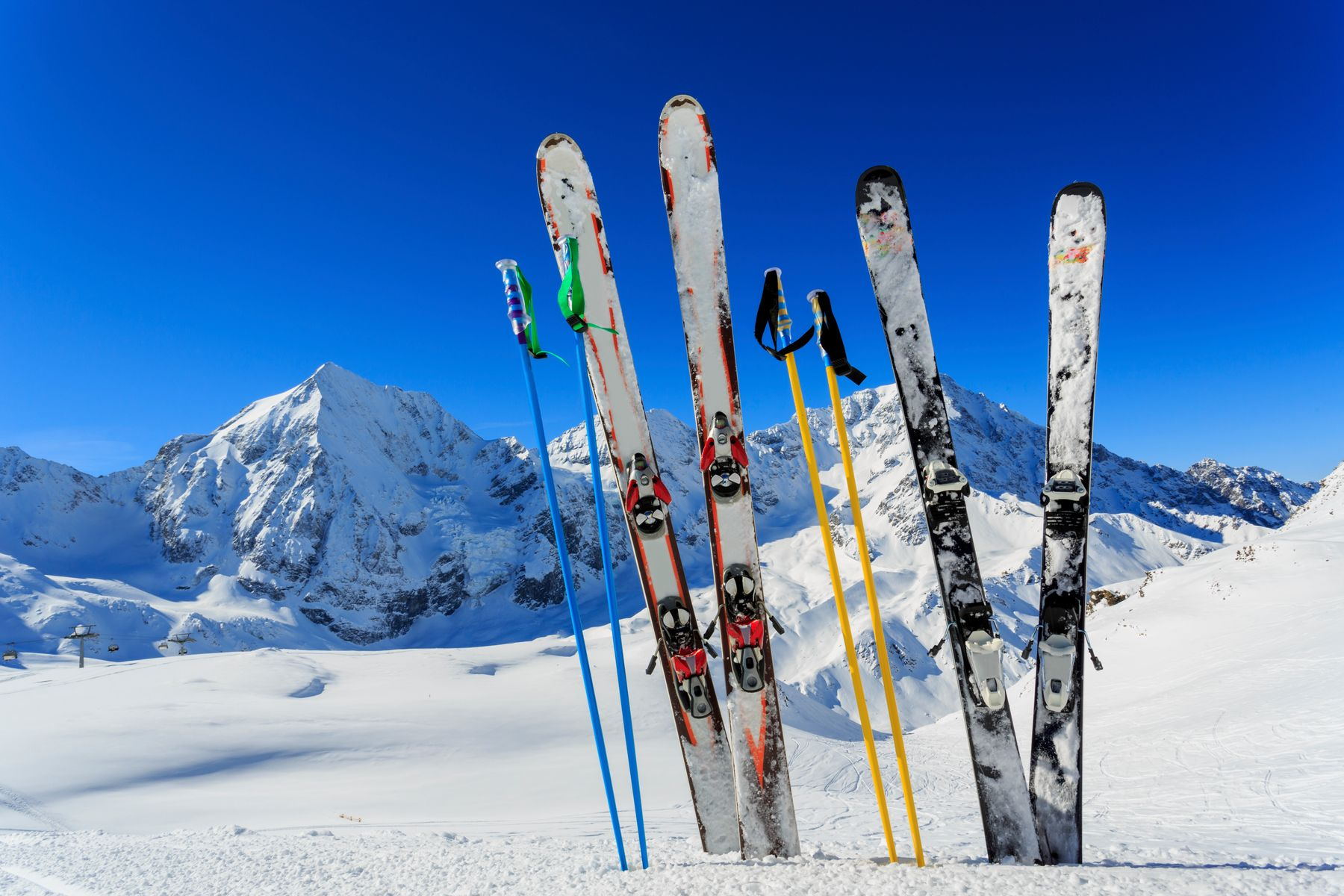 Two sets of skis and ski poles (sticks) are propped up in the snow, with mountains in the background