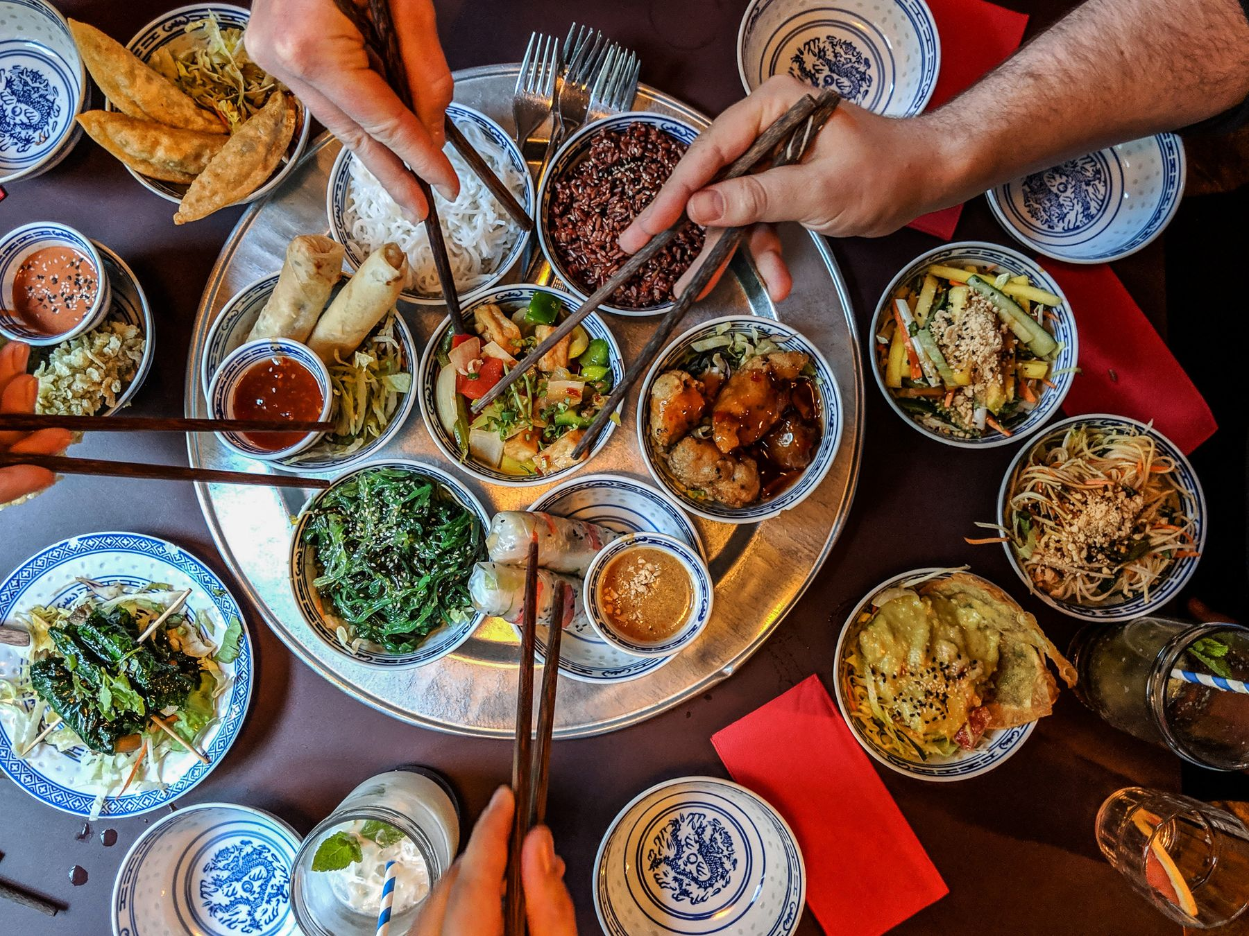 Diners dig into a mixed platter of Chinese food with their chopsticks.