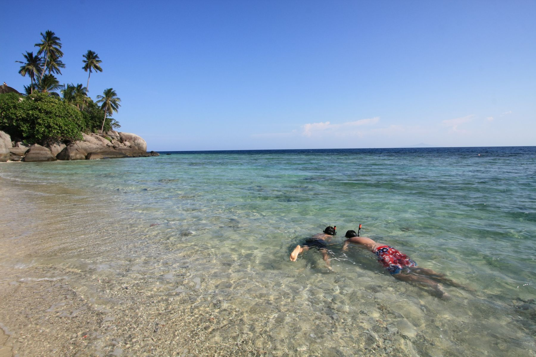 Kids snorkelling on a quiet beach.