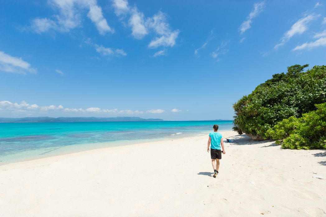 Man walking in tropical lagoon paradise of Okinawa - when is the best time to visit Japan
