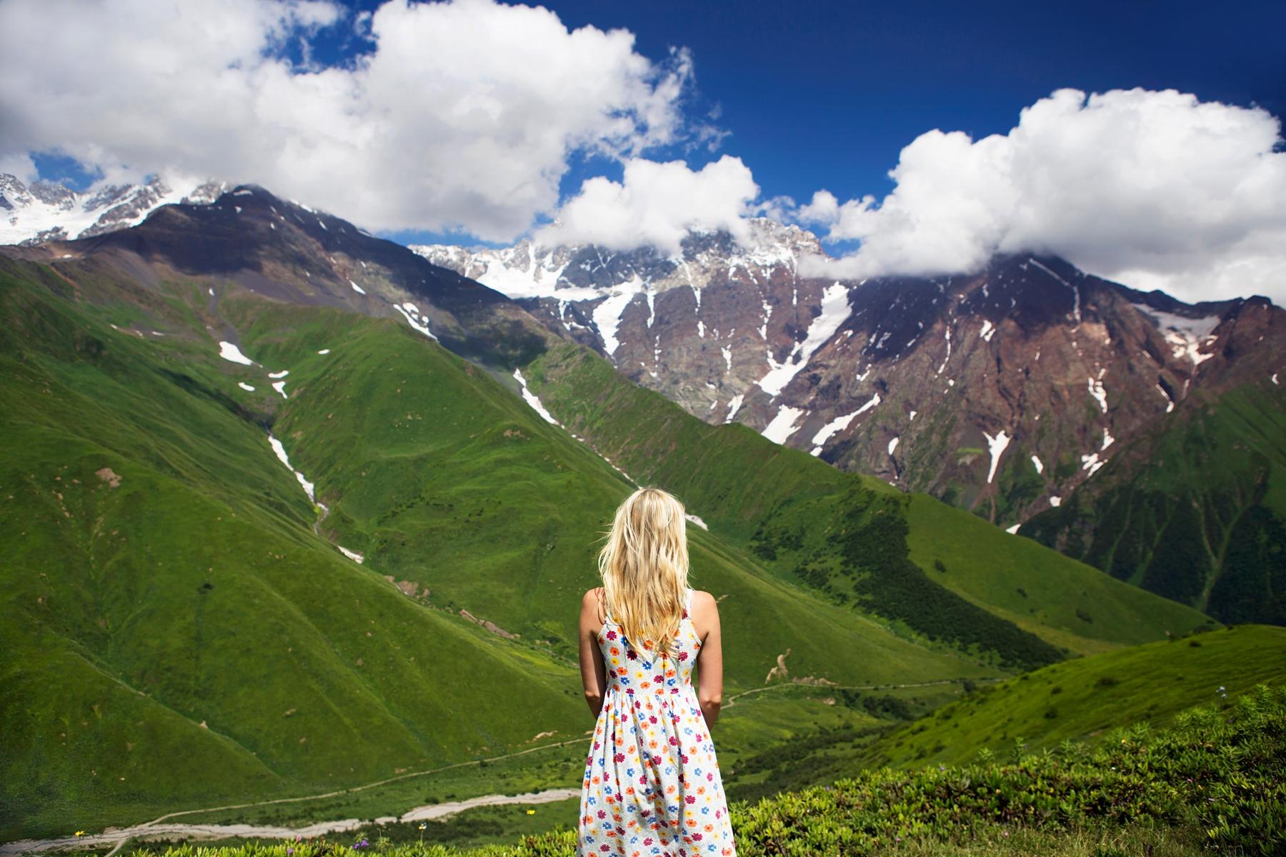 Девушка в летнем платье на фоне восхитительных грузинских гор