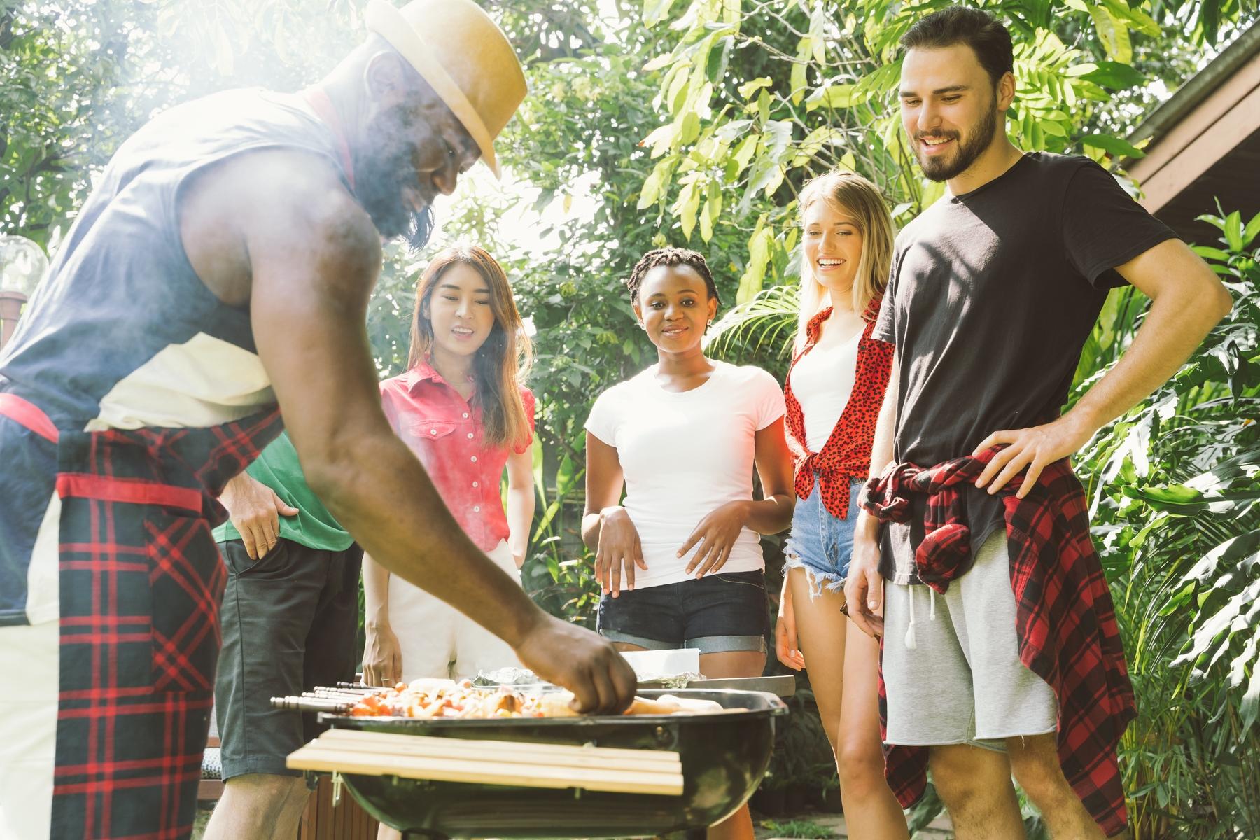 Pessoas fazendo churrasco na área externa de um hostel.