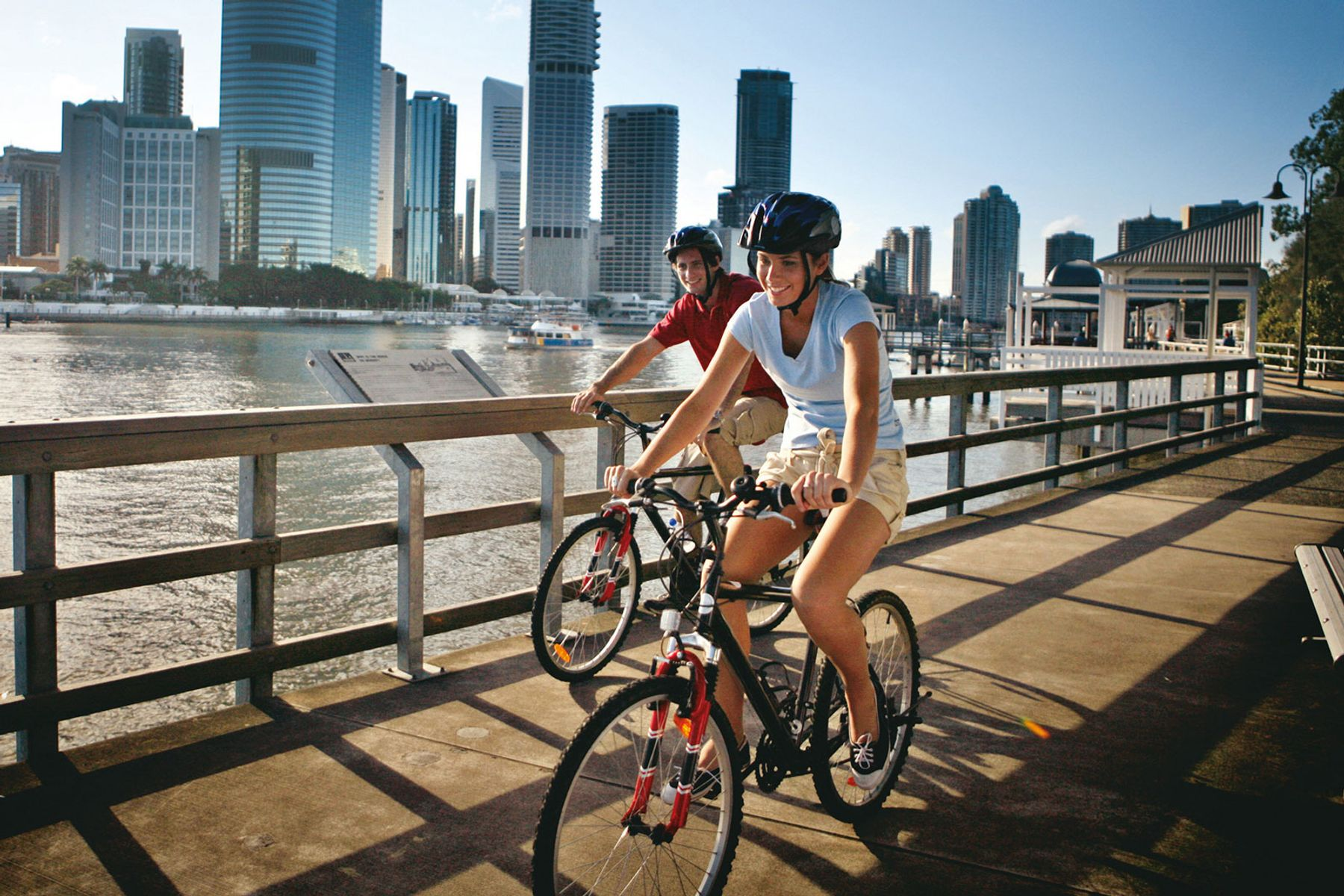 Two people cycling on the Brisbane River Walk pathway