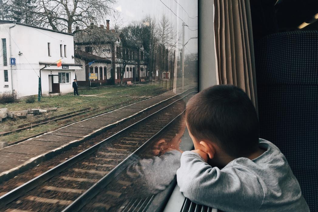 Παιδί θαυμάζει το τοπίο απ' το παράθυρο του τρένου -  συμβουλές για φθηνές διακοπές με παιδιά