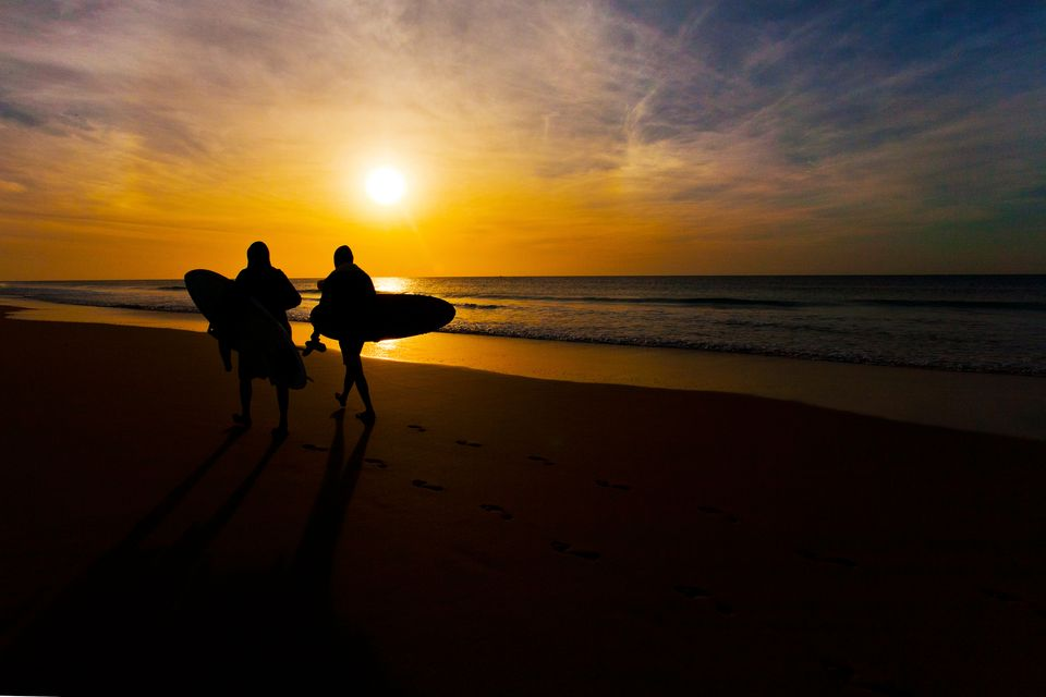 Two surfers walk on a beach at sunset