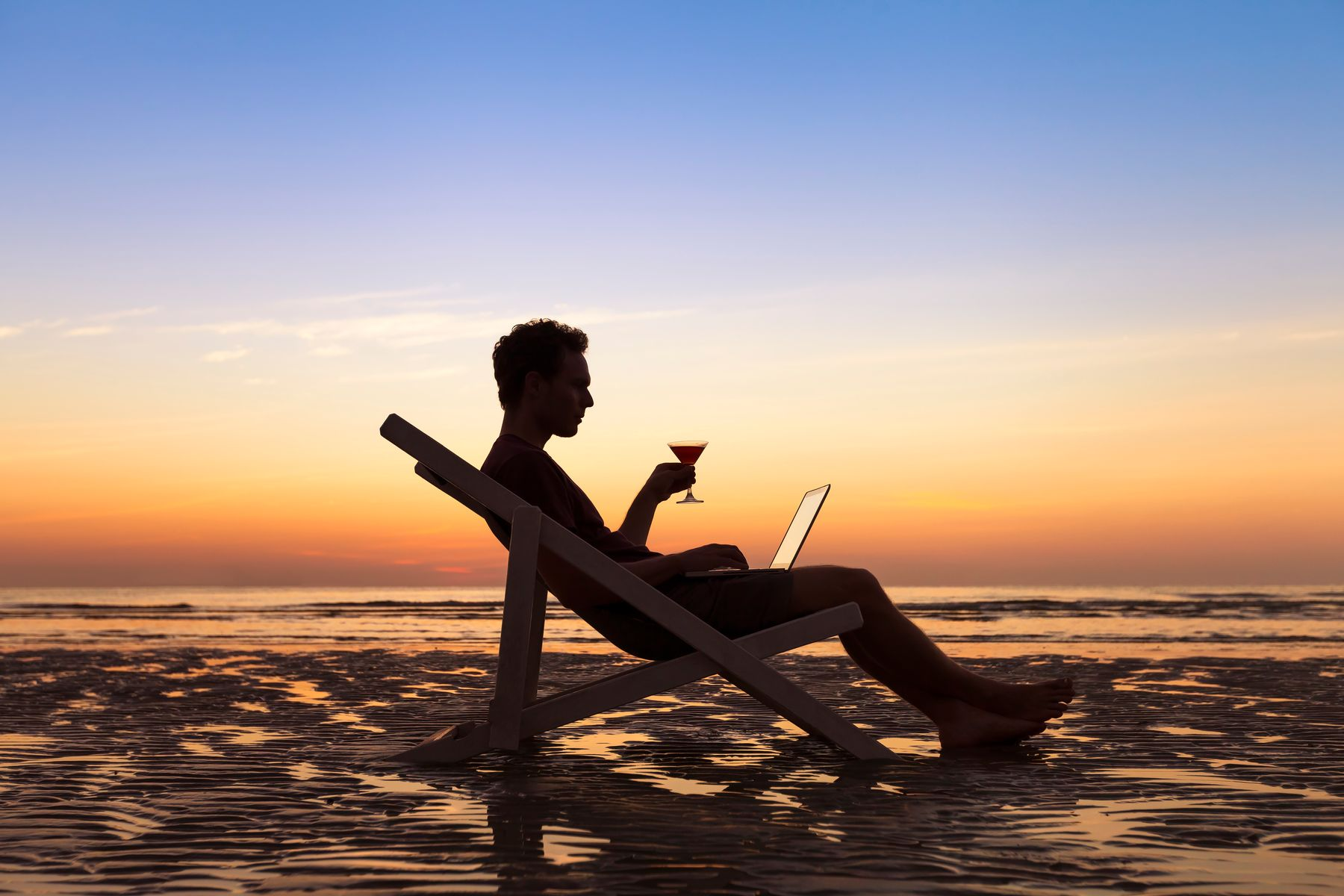 man sitting in lounge chair on beach working on a laptop during workcation