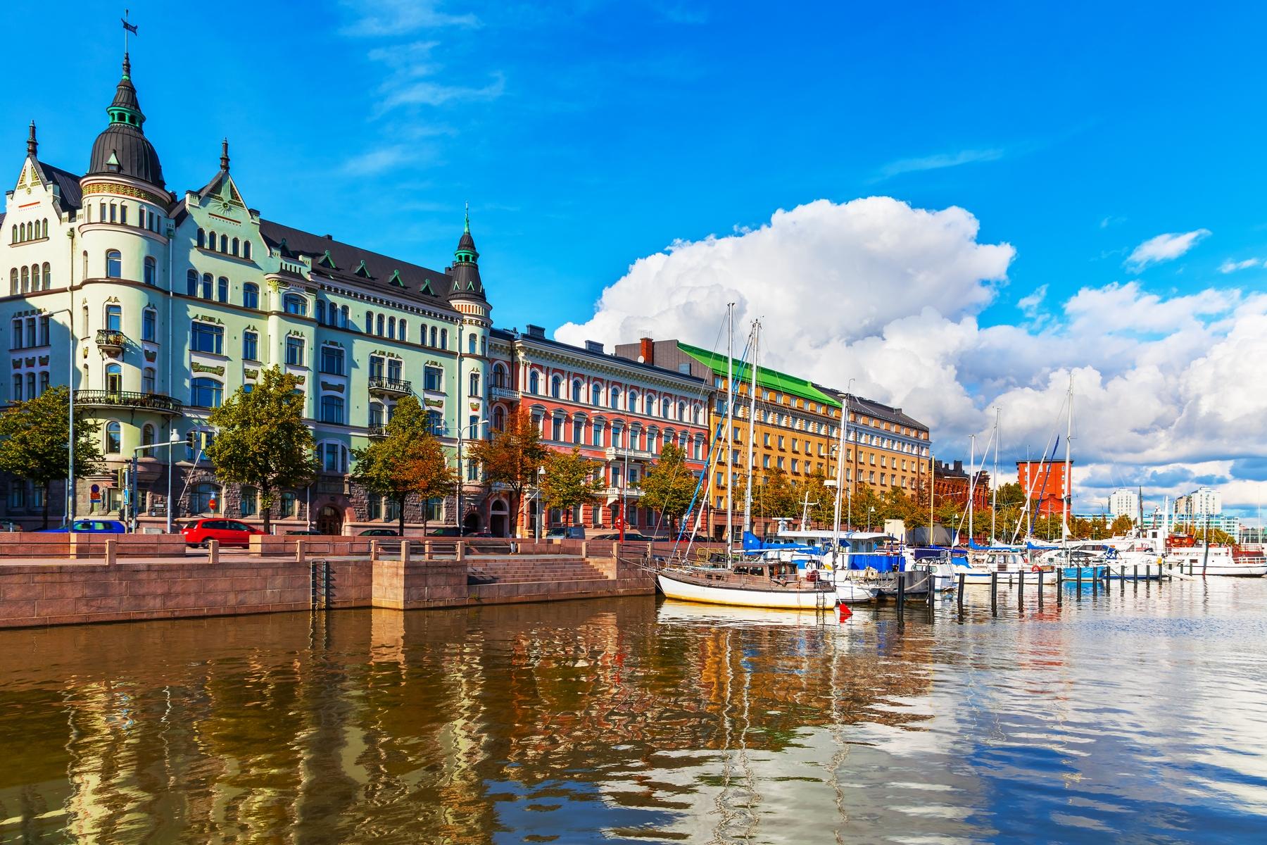 Boote am Wasser vor bunten Häusern am nachhaltigen Reiseziel Helsinki in Finnland