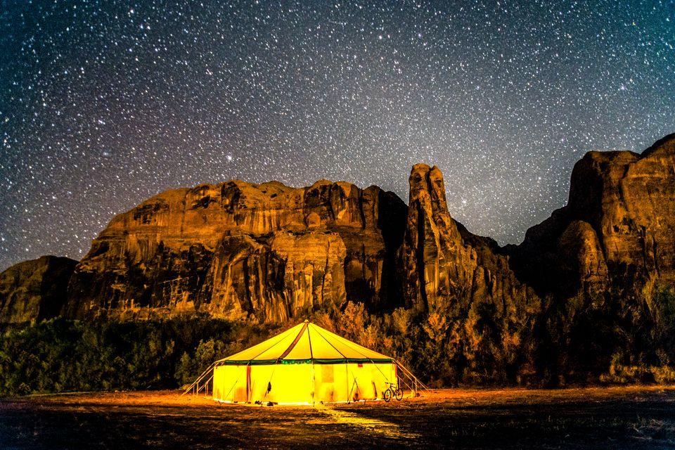Большая палатка-шатер звездной ночью в горах с припаркованным велосипедом