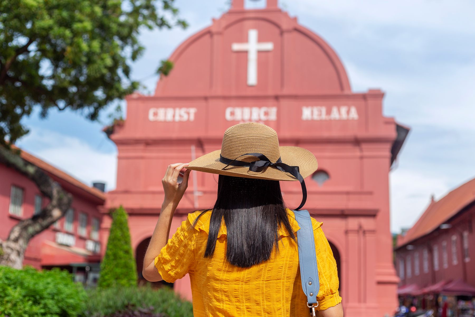 Solo female traveller in Melaka, Malaysia, looking at pink coloured church