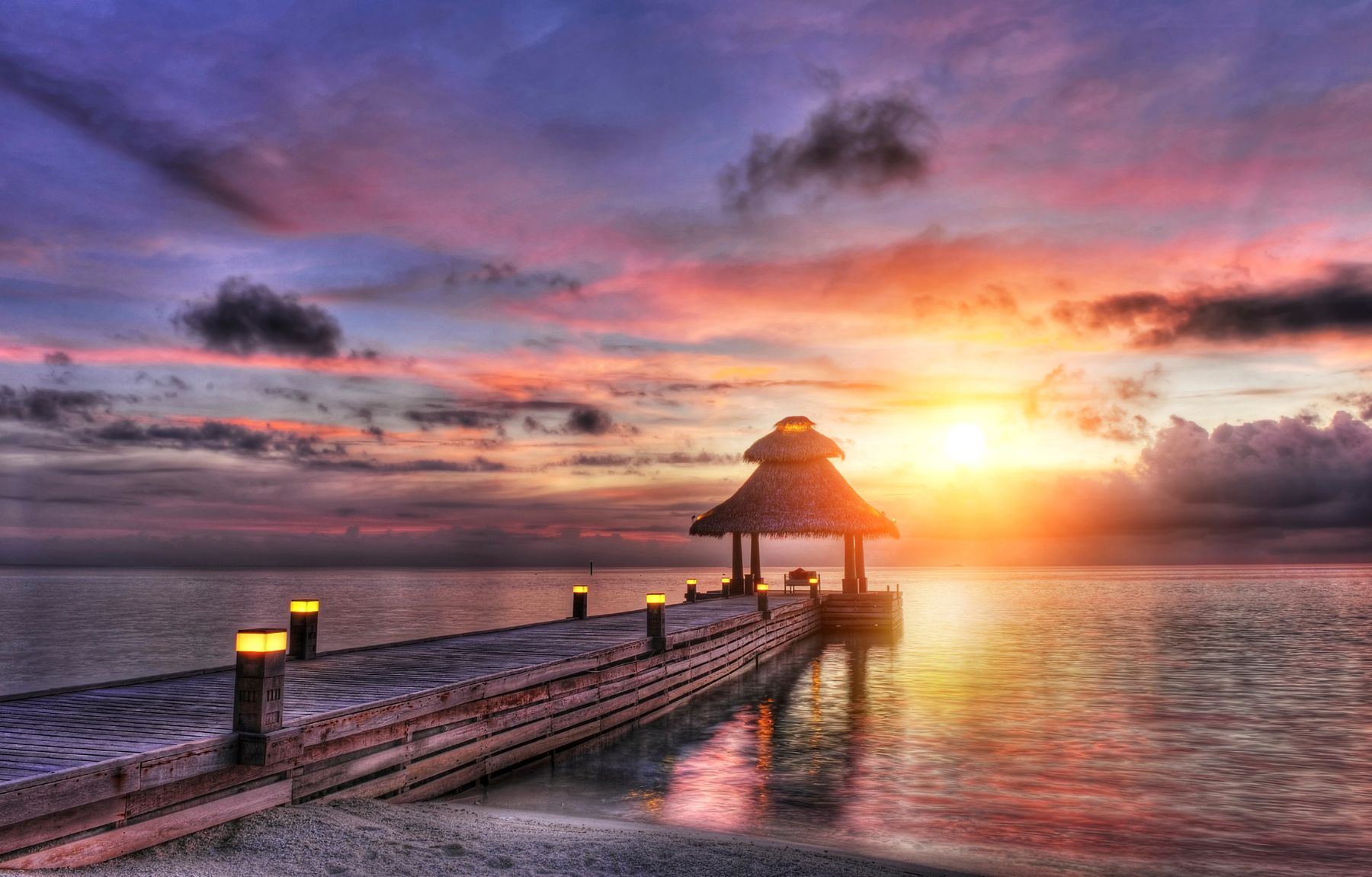 water dock with small patio overlooking a sunset over the ocean. Looking for a warm place to travel in December? Check out the Maldives.