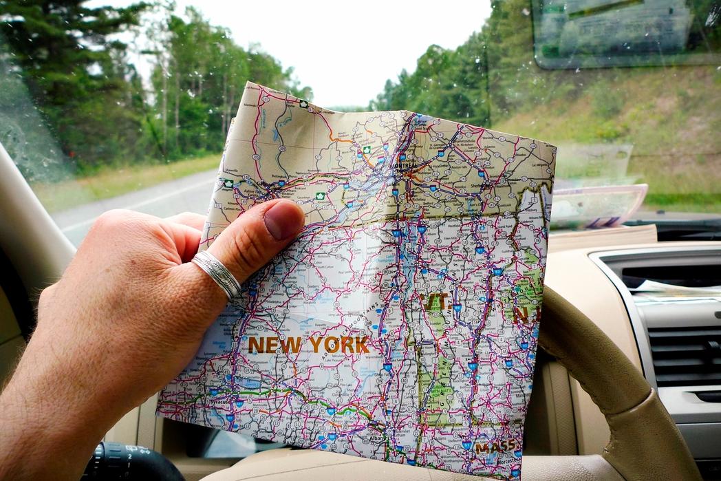 Οδηγός κοιτάζει τον χάρτη πάνω στο τιμόνι