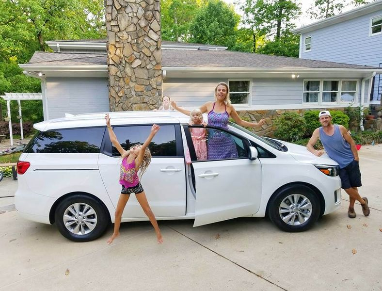 family standing outside of parked car excited for their road trip