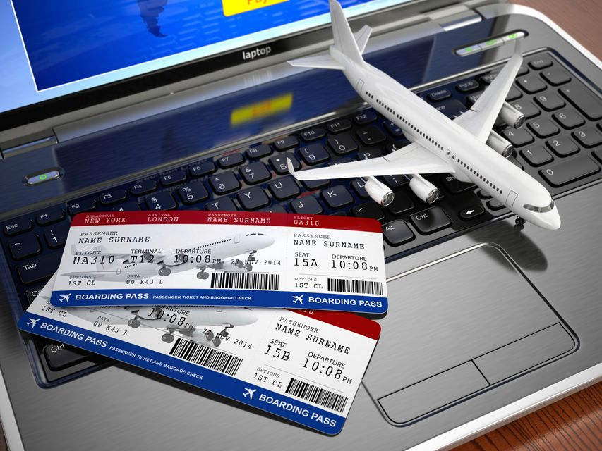 Laptop with tickets and a toy plane on top