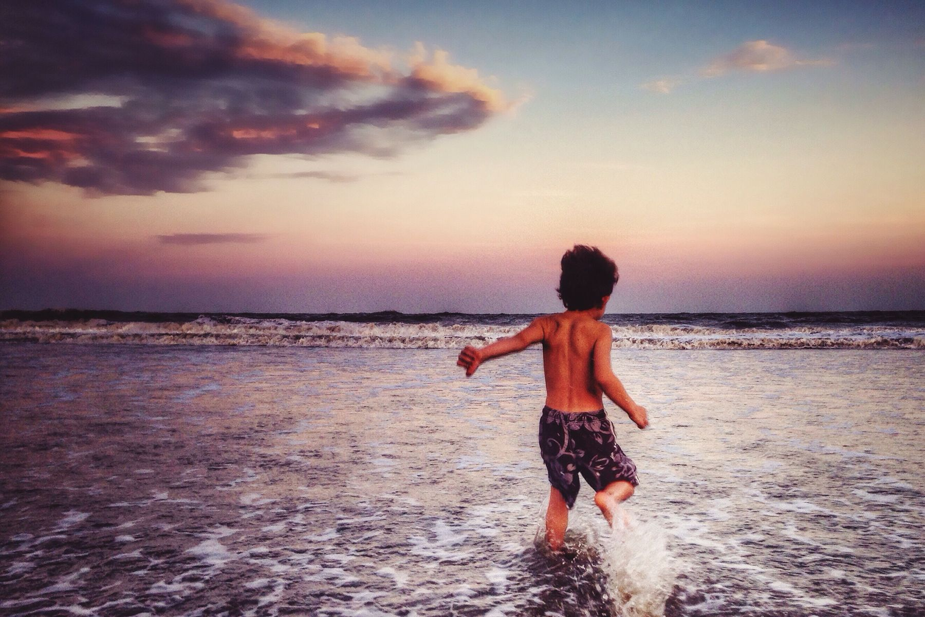 Small boy wearing patterned swim trunks running into the ocean at sunset
