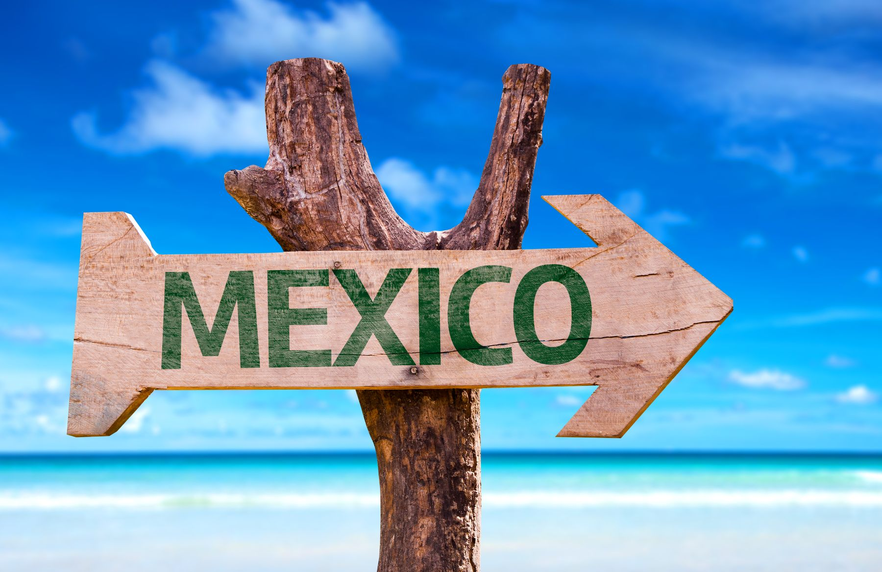 sign by the beach pointing towards Mexico