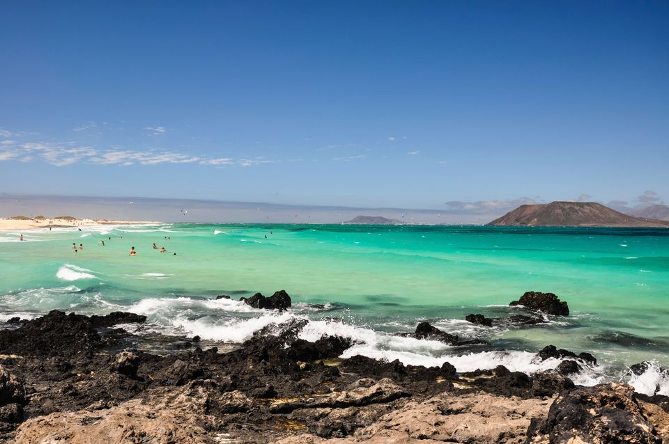 Volcanic beach in Fuerteventura with turquoise waters and people playing with the waves
