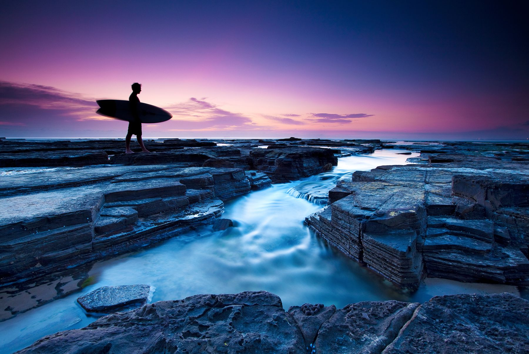 Silhouette of a surfer at dusk. Surfboards will incur extra Spirit baggage fees.
