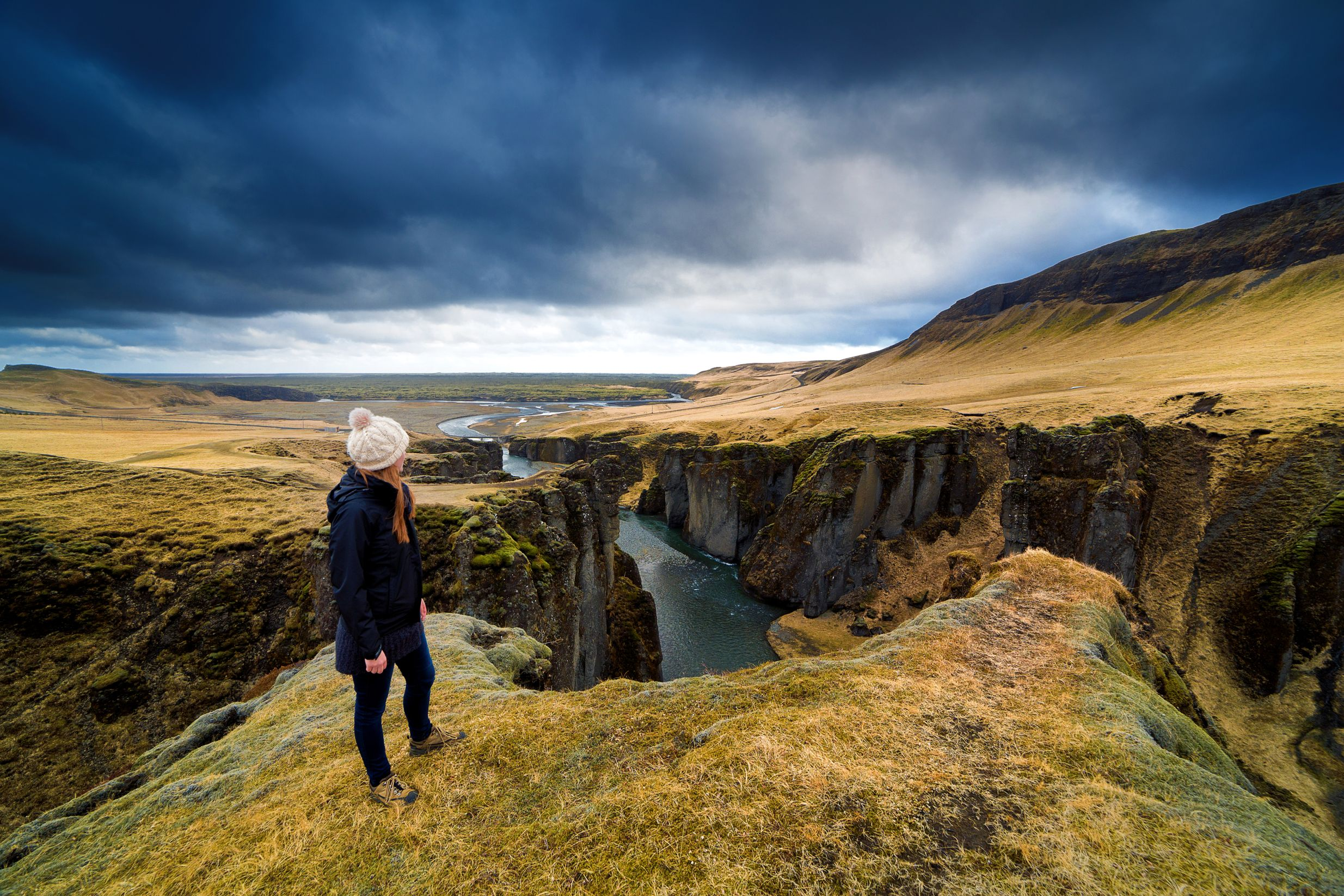 Young woman wearing black coat and white hat looks out on dramatic landscape of Fjadrargljufur canyon under dramatic stormy skies.