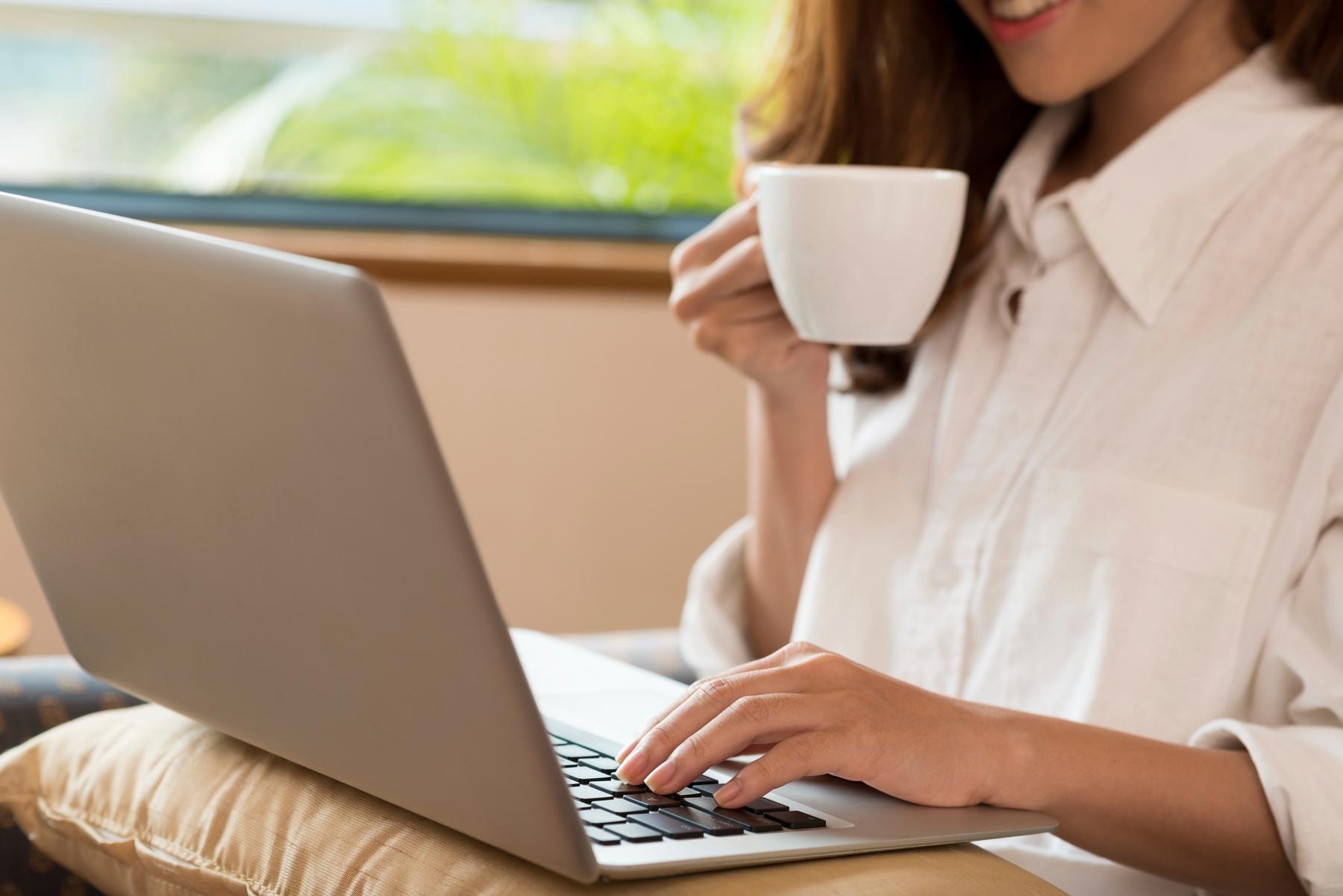 Mulher com uma xícara na mão direita, digitando com a mão esquerda no teclado de um notebook.