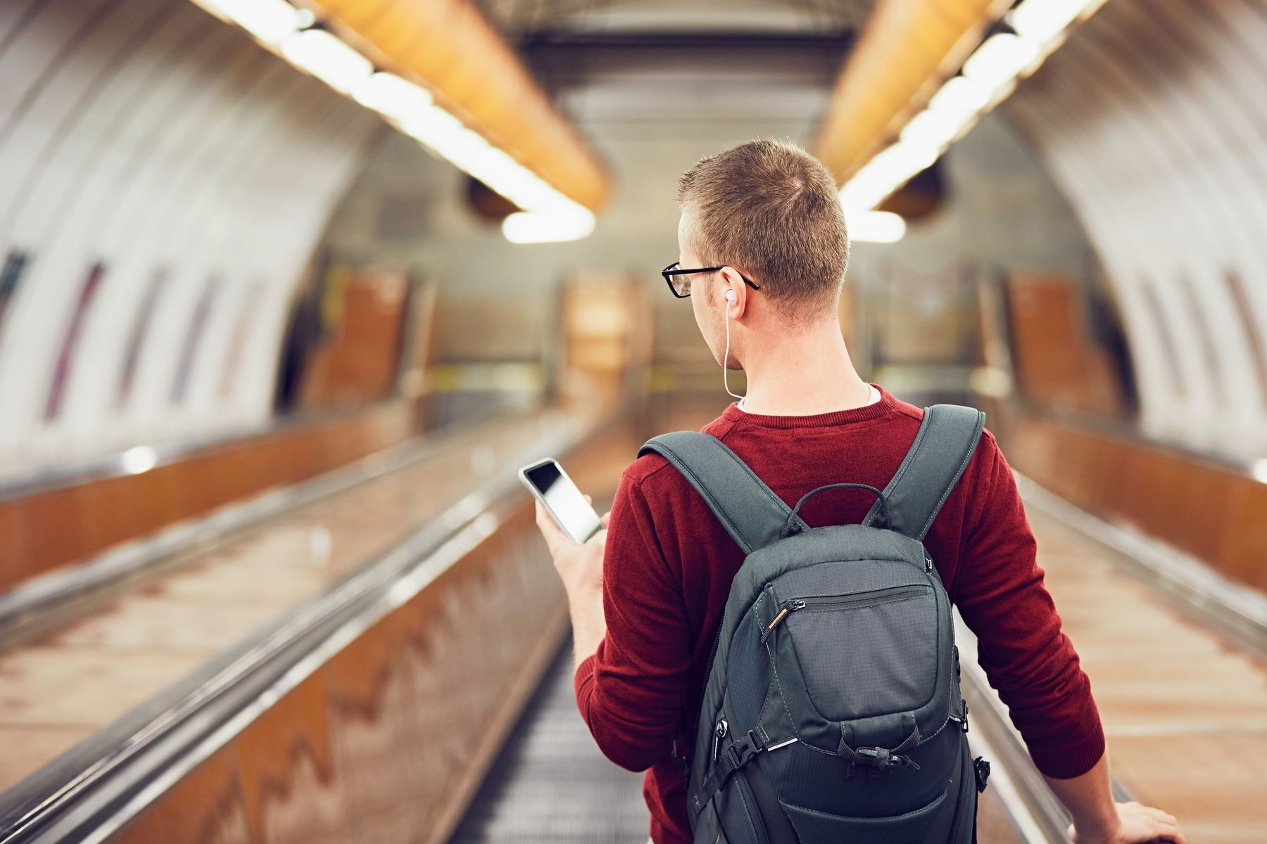 Young man checking his phone in an underground train station