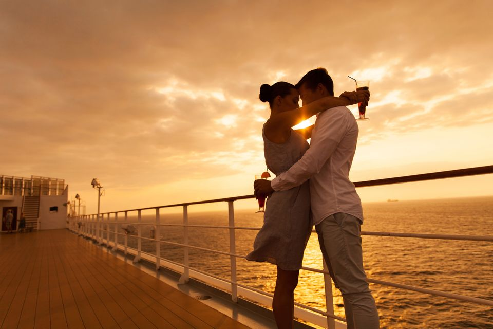 A couple on a boat at sunset, with wine.