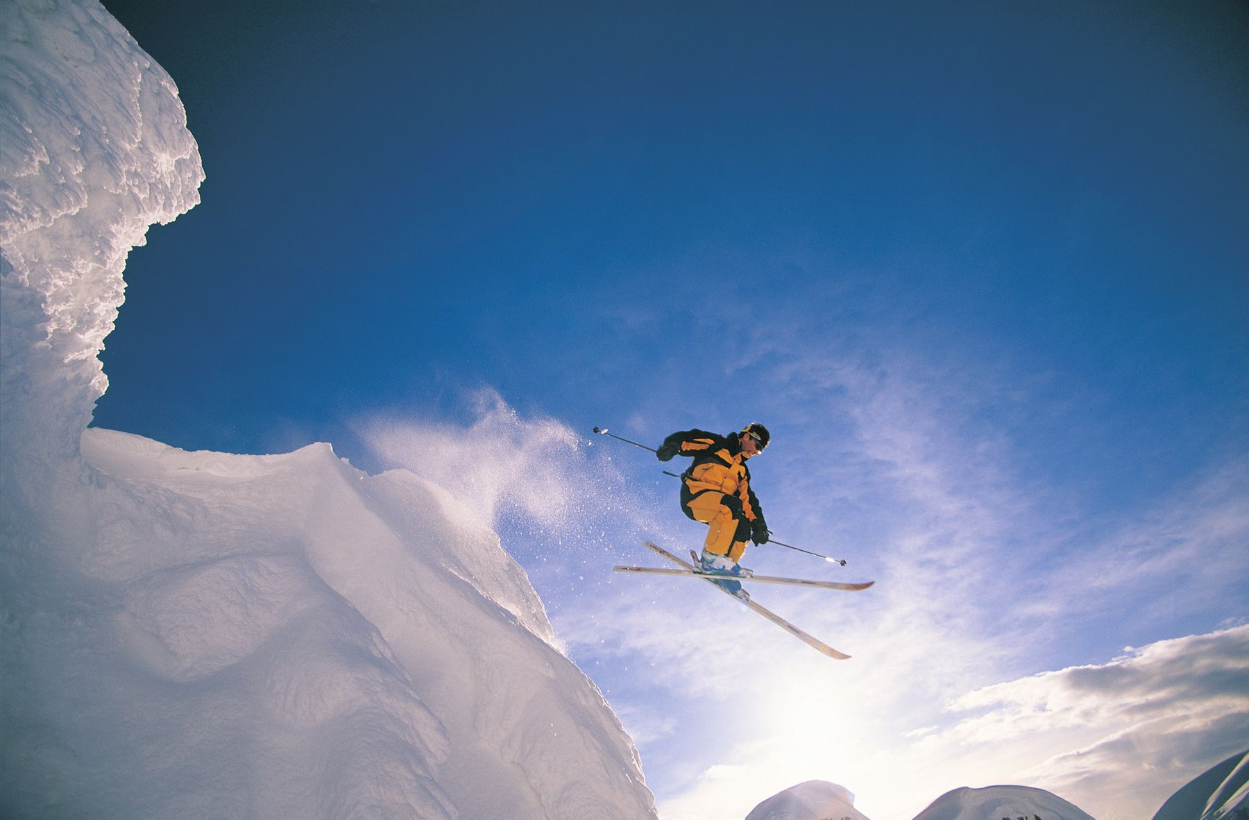 A skier floats mid-air as they have just passed an elevated ledge.