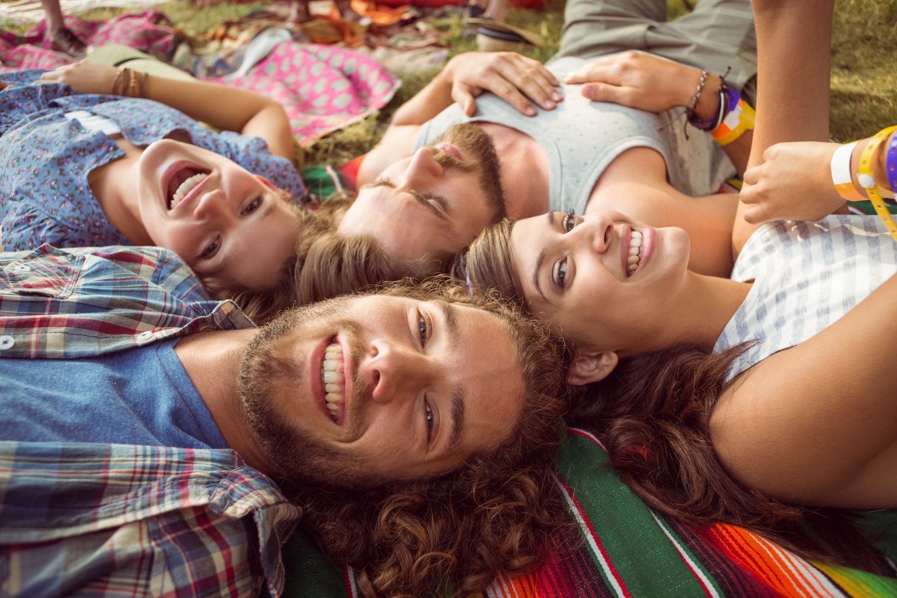 group of friends resting on a blanket on the ground in summer