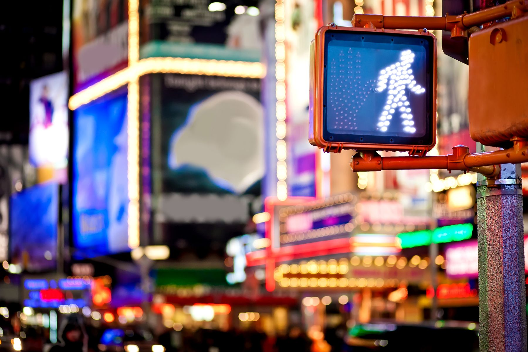 Focus on a pedestrian traffic light, with the bright lights of a big city blurred in the background.