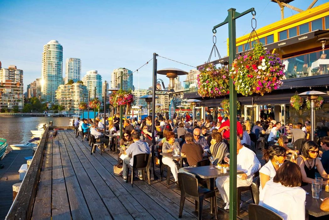 People dining on a patio on Granville Island in Vancouver on a summer afternoon