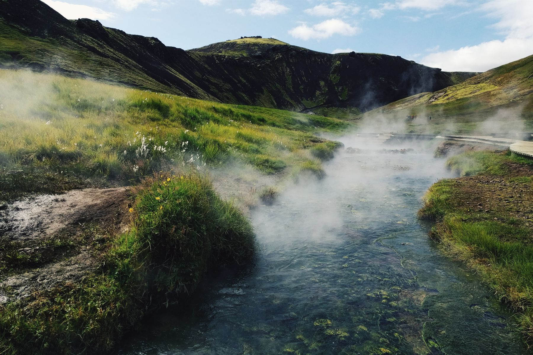 Steam rising off a river in Iceland, surrounded by bright green mossy grass with hills in the background