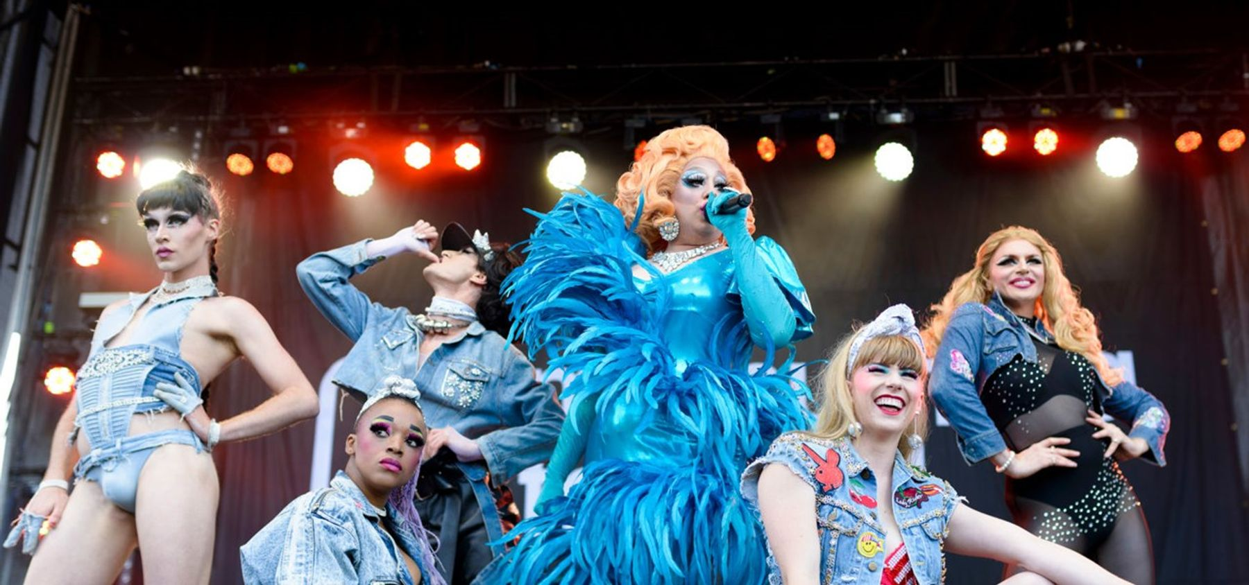 Six people putting on a drag show, posing. Some cities will be able to have live, in-person events like this for Pride 2021.