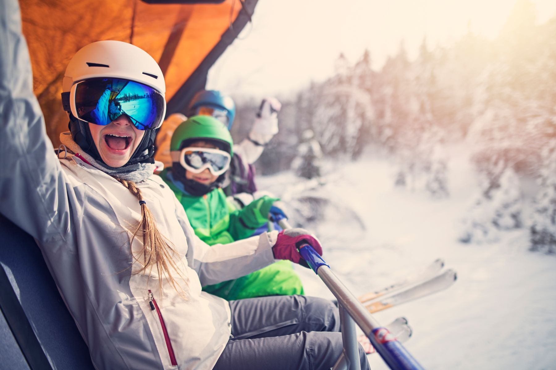 A family sitting on a ski lift and cheering at the camera, while the sun sets over an Alpine landscape