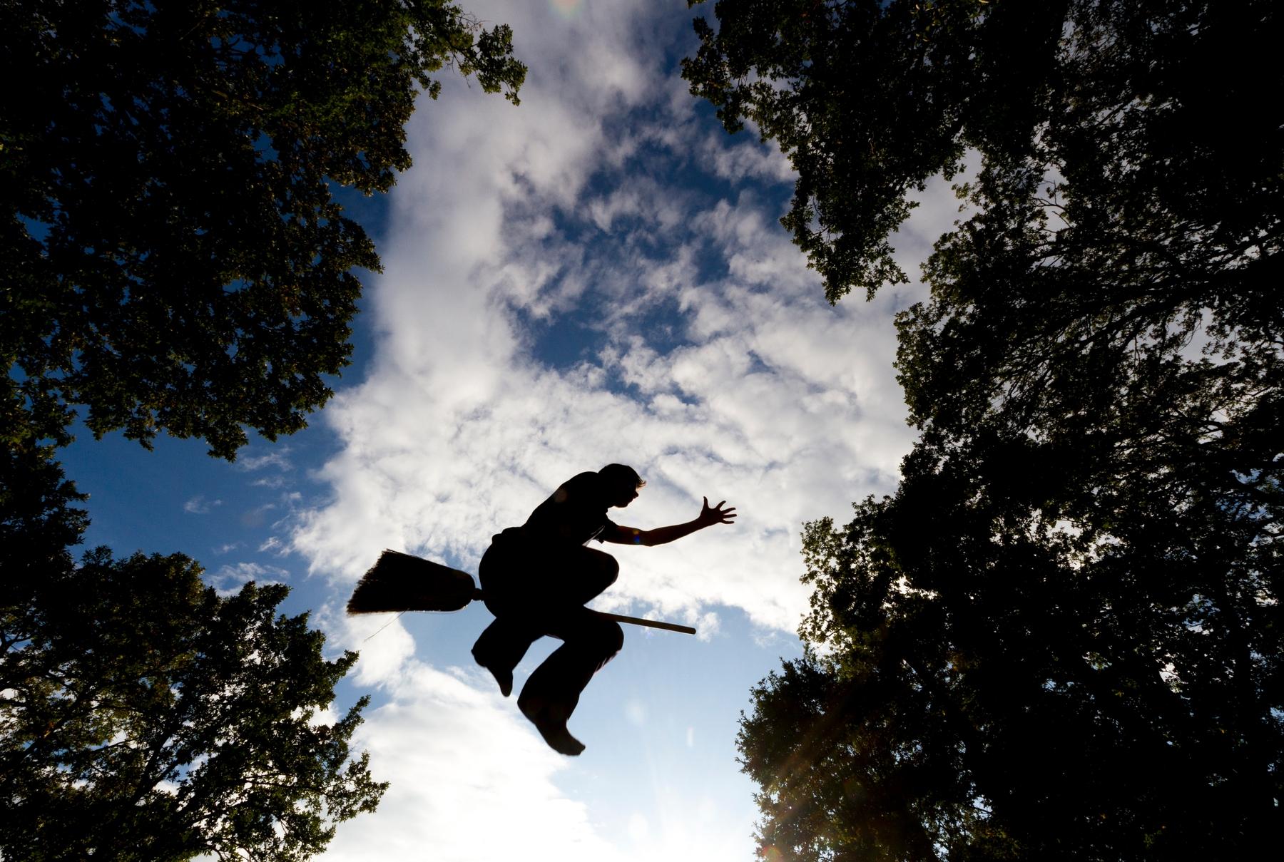 Силуэт человека на летающей метле на фоне неба и деревьев