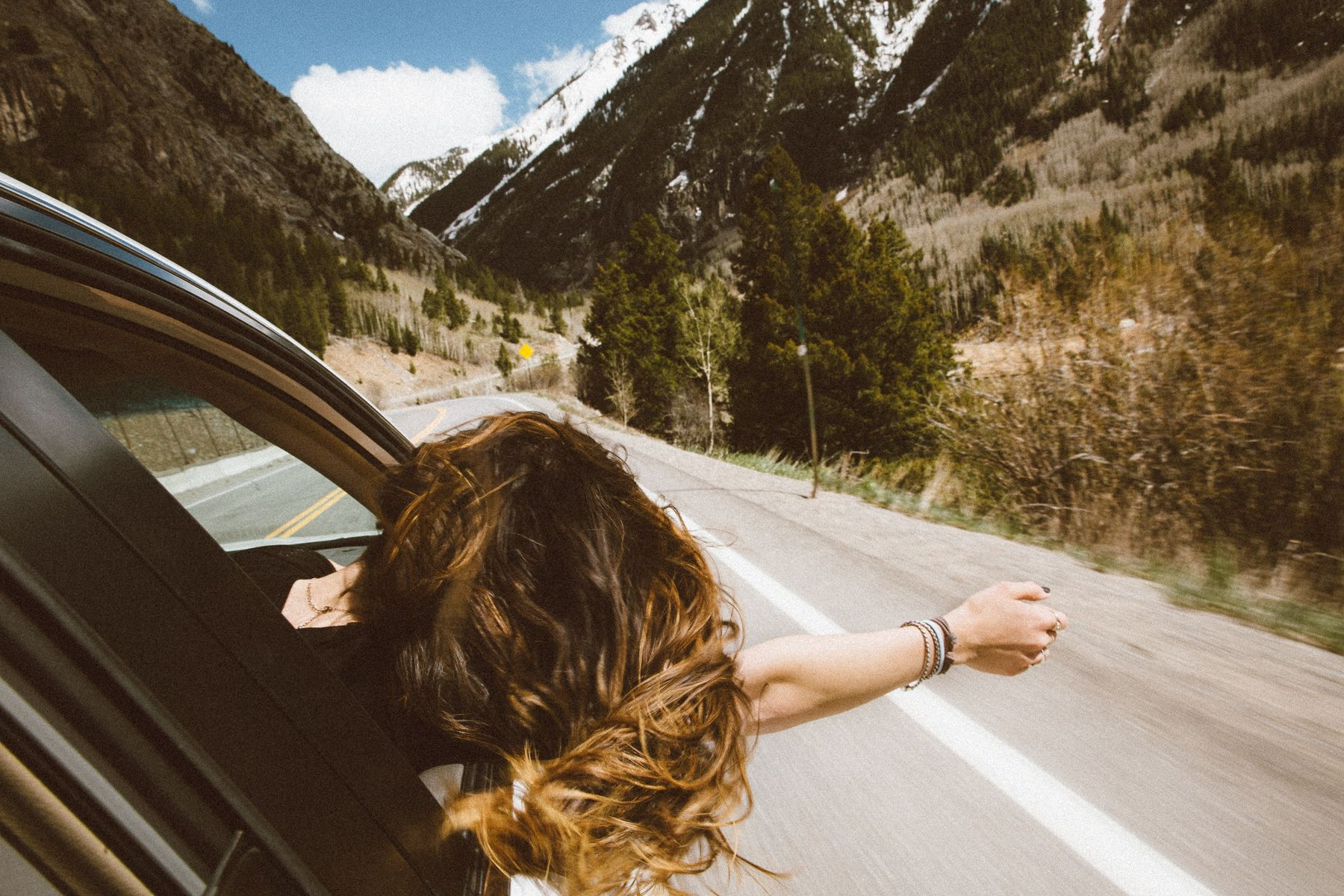 girl hanging outside car window during road trip