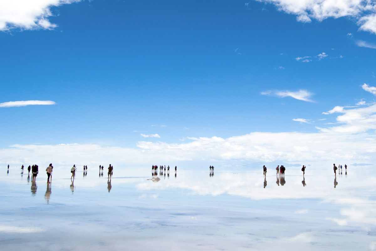 People walk on lake Salar de Uyuni in Bolivia, which fades into the sky - one of the most magical places in the world