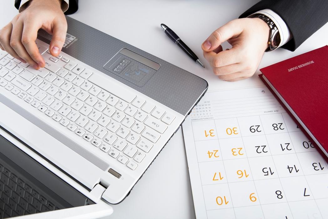 Άντρας κρατάει ημερολόγιο στον υπολογιστή
