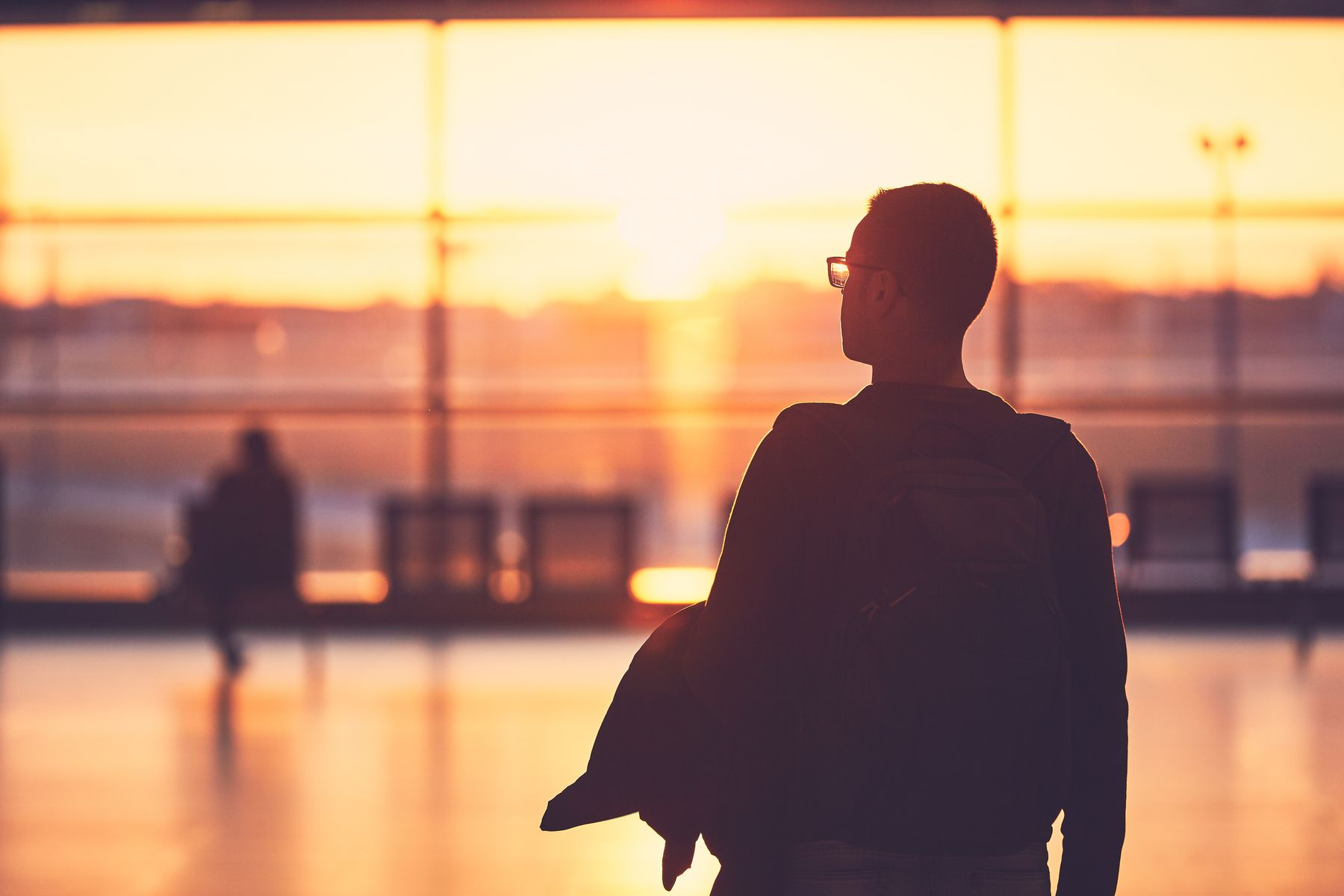 Man looking out the window at sunset inside an airport