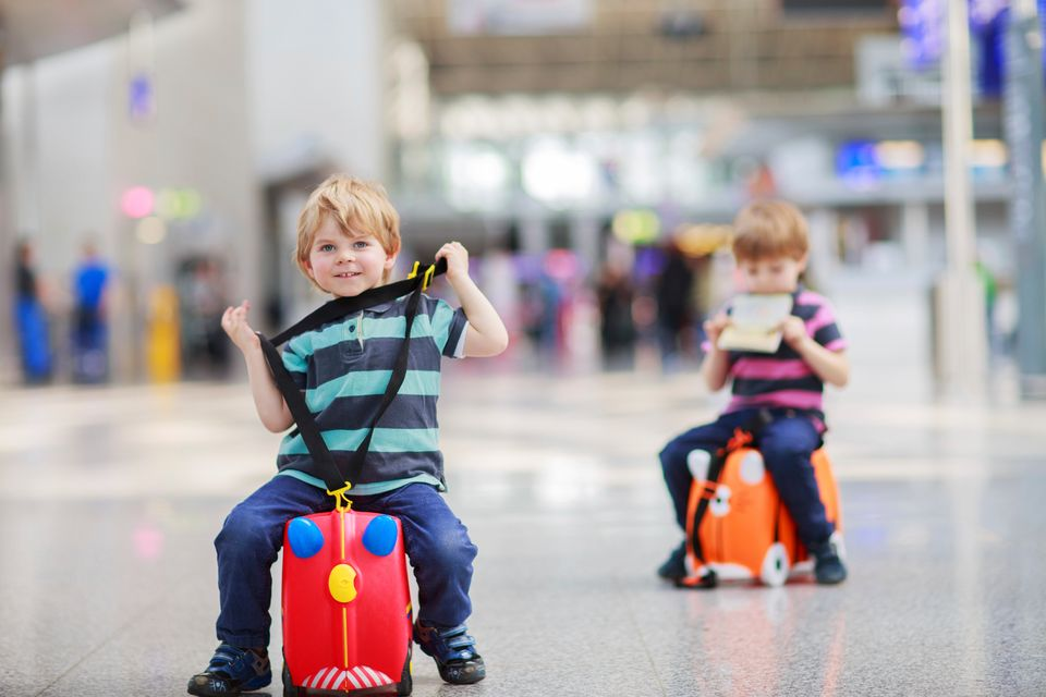 Μικρά παιδιά κάθονται στις βαλίτσες τους και παίζουν μέσα στο τερματικό σταθμό αεροδρομίου