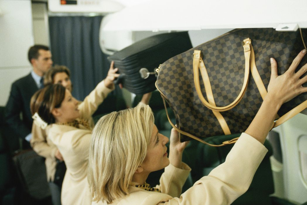 Cabin crew putting cabin baggage in overhead locker