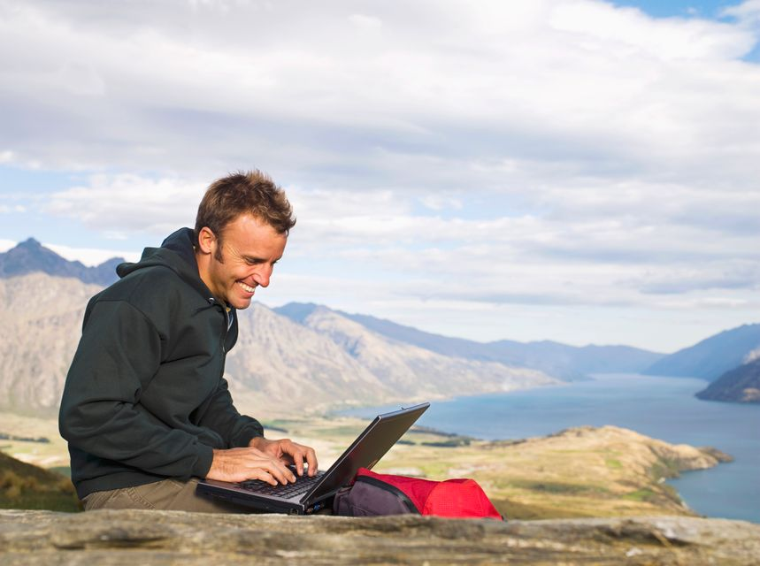 """""""Mixed race hiker using laptop on remote hilltop, Queenstown, South Island, New Zealand"""" - how to find the best flight sale flights"""