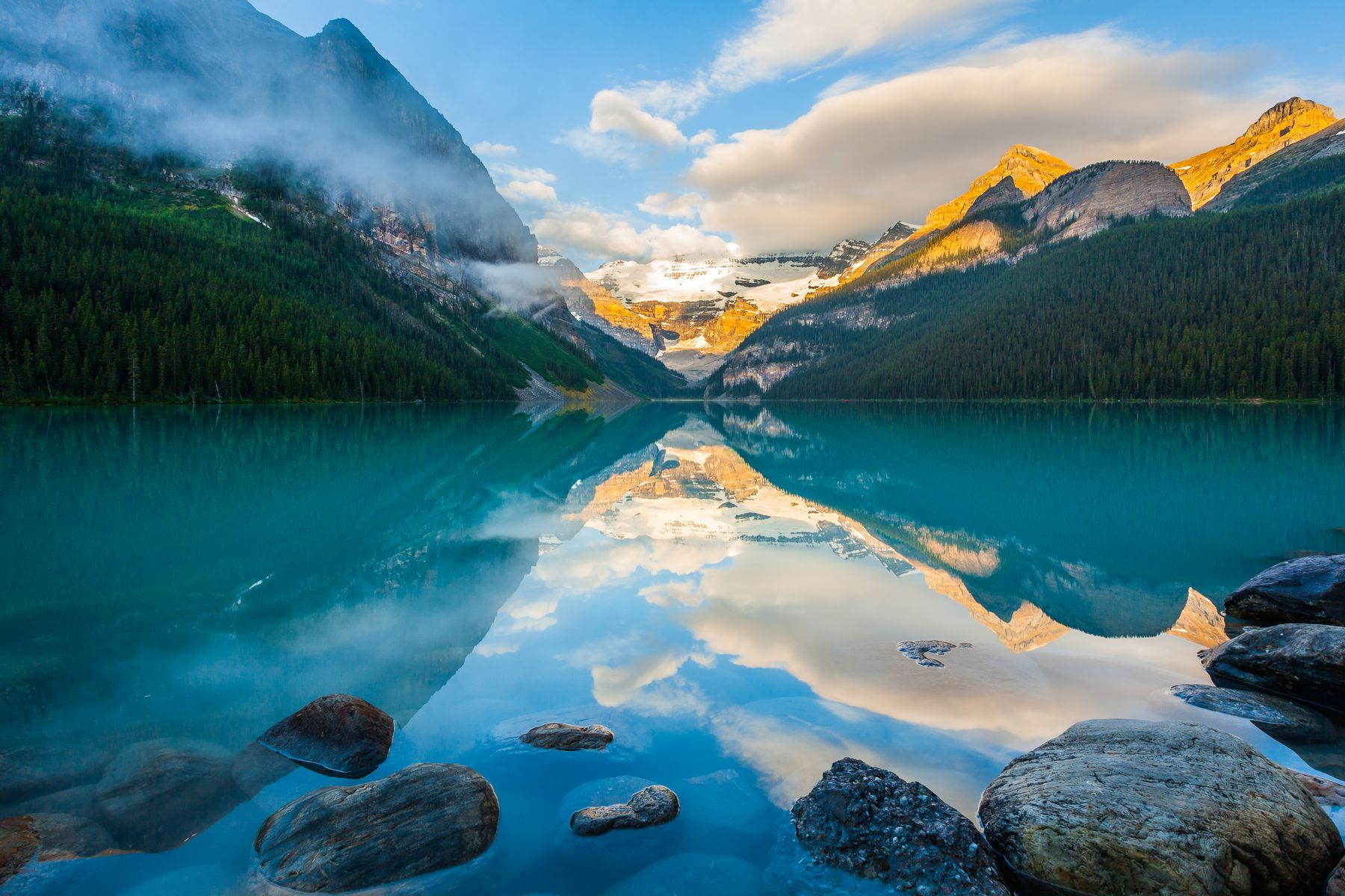 turquoise hues of Lake Louise with snowy mountains in the backround