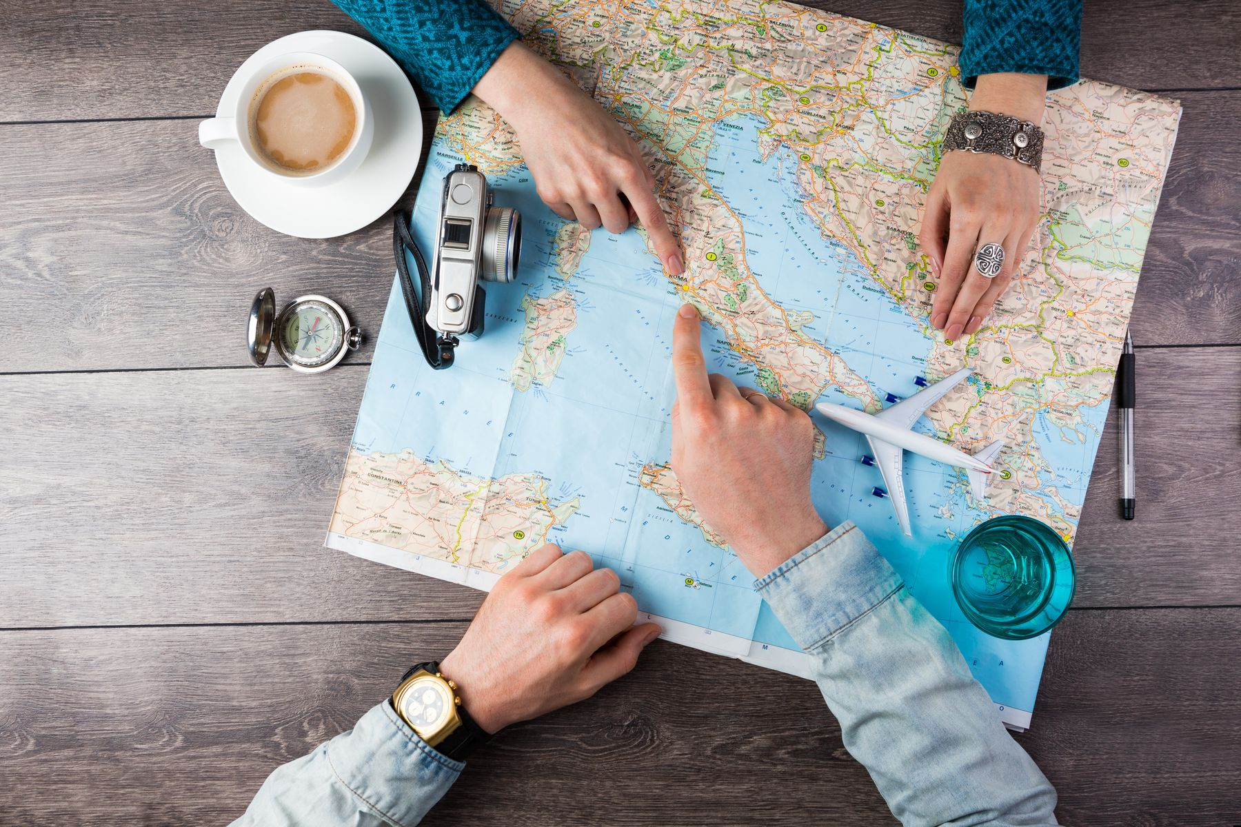 The hands of a woman and man point at a map of multi city flight plan. There is a camera, a coffee cup and a compass.
