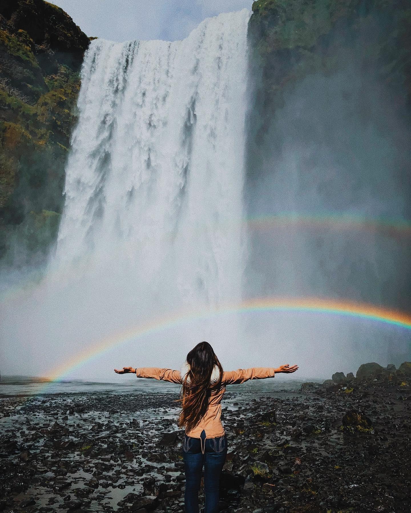 Девушка на фоне радуги у водопада в Исландии