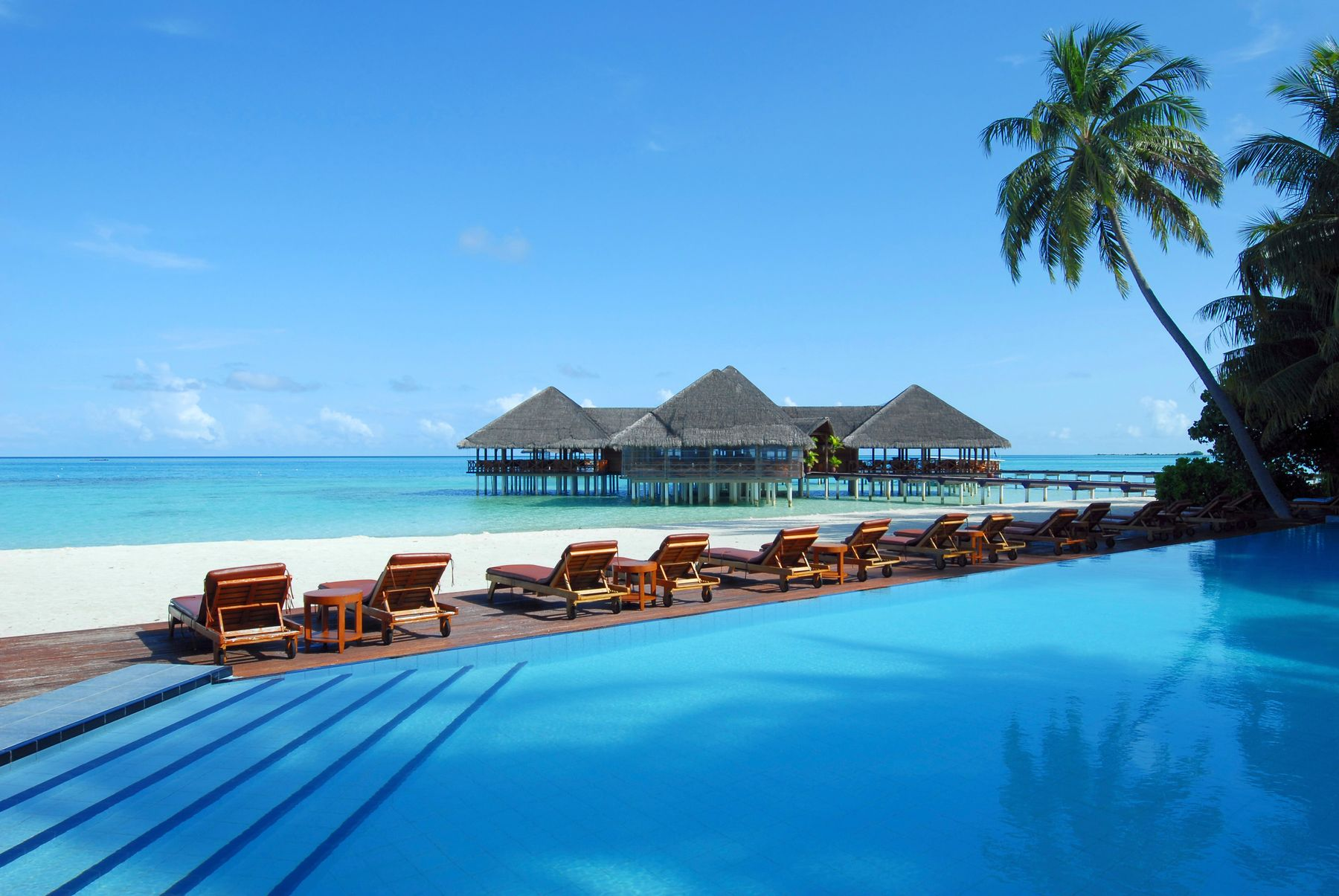 Sun loungers looking out to sea in The Maldives. In the background are over-water bungalows and the foreground features a swimming pool