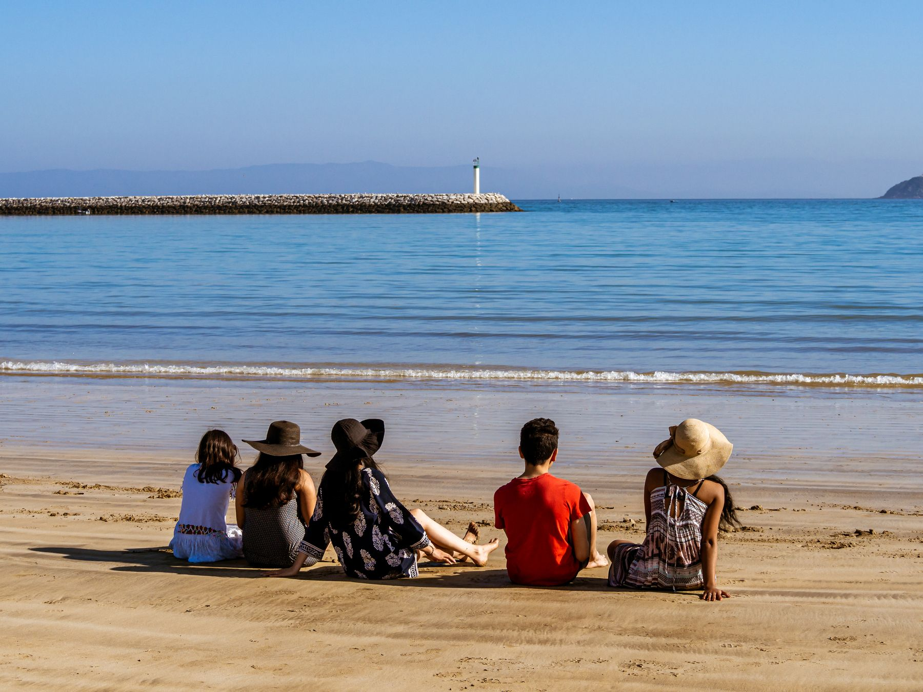 Rear view of people sitting on the municipal beach of Tangier in northern Morocco