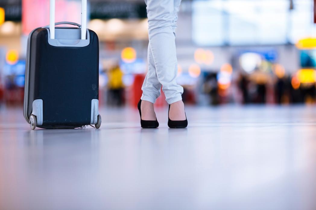 Nainen vetää perässään pyörillä kulkevaa matkalaukkua