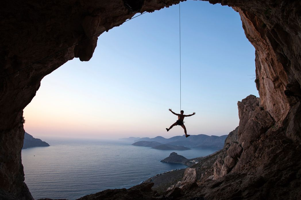 Climber watching sea view at rock window on Kalymons - best Greek island to vist for adventurers